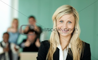 Businesswoman in front of her team in an office
