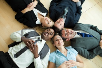 Business people lying in a circle on the floor