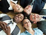 Closse-up of business people lying in a circle on the floor