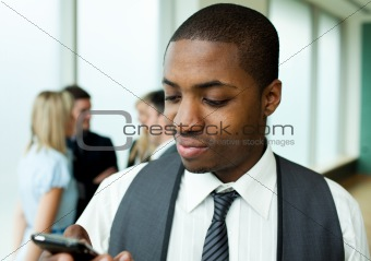 Afro-American businessman texting in office