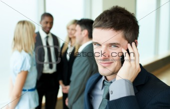 Smiling businessman on phone in office