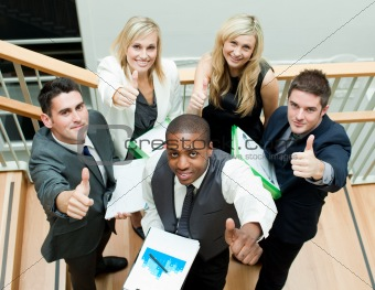 Business team having a meeting on stairs with thumbs up