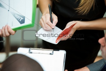 Business people writing on notes