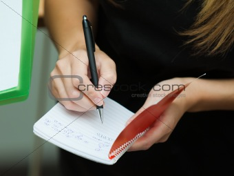 Blonde businesswoman writing on a notebook