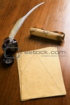 Old paper, quill pen and scroll on wooden table