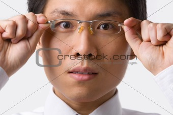 Asian businessman holding glasses to camera