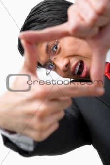 Asian businessman looking at his perspetive by framing his finge