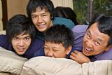 Father and sons having fun in bedroom