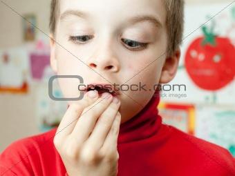 Boy holding missing teeth