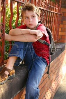 Boy with schoolbag slung over shoulder