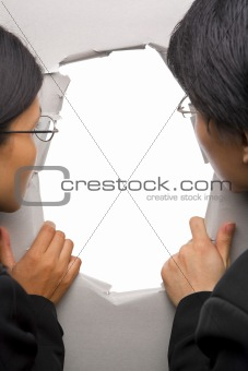 Business people peeking through hole in wall