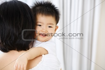 Asian toddler on her mother hug