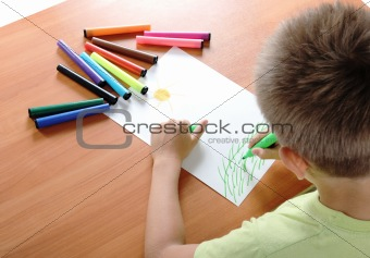 child draws green grass and sun on white paper by colour pensil