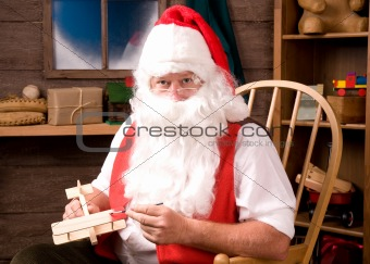 Santa Claus painting toy airplane in his workshop