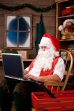 Santa Claus in Workshop Using Laptop