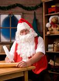 Santa Claus Sitting in His Workshop with Quill Pen