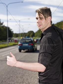A young man hitchiking on the road