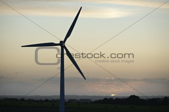 a wind mill with a snset in the baground with very rich colours