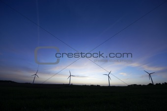 Abstract wind turbines at night.