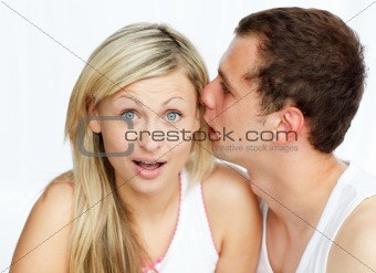 Man telling a woman a secret