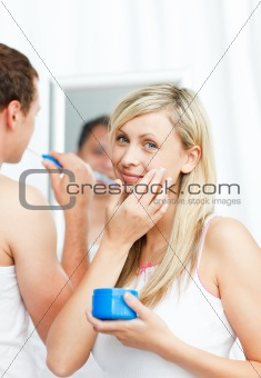 Beautiful woman putting cream on her face