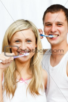 Couple cleaning their teeth smiling at the camera