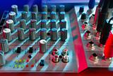Audio mixer music desk under colorful lights