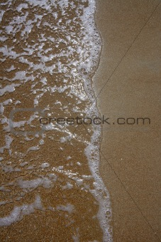 Close up of coastline with wave reaching the sand