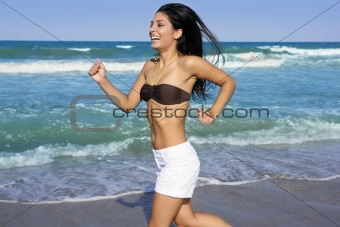 Beautiful summer brunette girl jumping on the beach