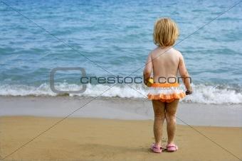 Blond little girl with sandy legs on the beach