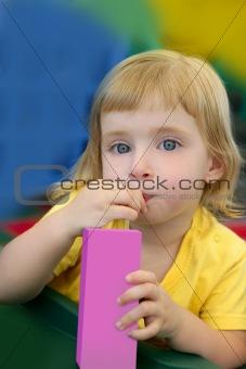 Beautiful blond girl drinking pink juice