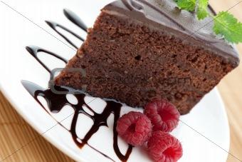 Slice of delicious chocolate cake with fresh raspberries