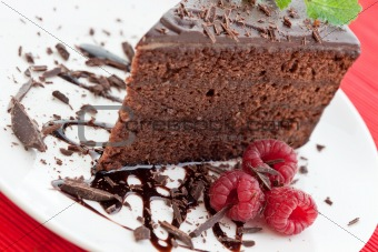 Slice of delicious chocolate cake with fresh raspberries
