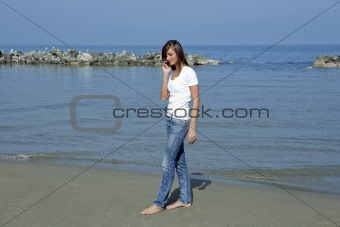 Beautiful woman barefoot by the seashore with a mobile phone