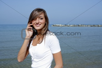 Beautiful woman by the sea with a mobile phone