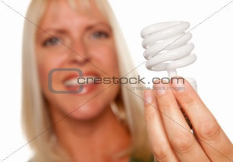 Attractive Blonde Woman Holds Energy Saving Light Bulb Isolated on a White Background with Narrow Depth of Field.