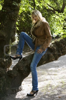 blond girl sitting on a branch
