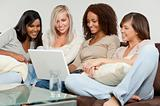 Four Young Women Friends Having Fun Using A Laptop Computer