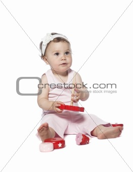 Baby in pink clothes playing with a red toy