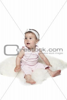 Baby sitting on a sheepskin