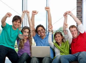 Excited friends with a laptop
