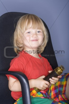 boy with long blond hair sitting in an office chair holding binoculrars