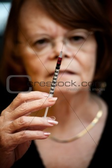 Senior woman with hypodermic needle
