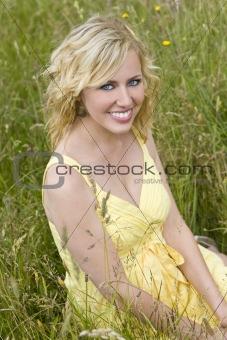 Beautiful Blond Woman Sitting In Tall Grass