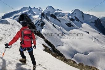 Mountaineer walks down along a snowy ridge