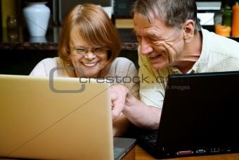 Senior couple using laptop computers at home