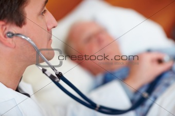 Doctor examining a senior man's heart beat with a stethoscope