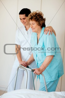 Senior woman being helped by a nurse to walk on a Zimmer frame