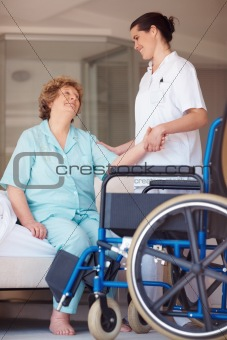 Nurse helping a senior woman onto a wheelchair