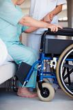 Low section Nurse helping a senior woman onto a wheelchair